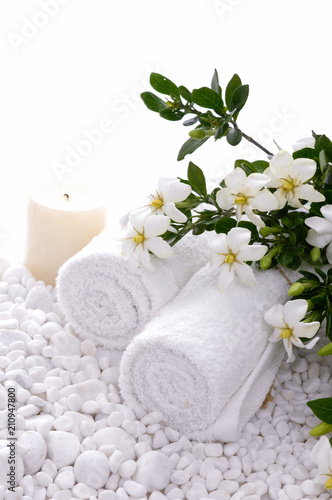 Deurstickers Spa Rolled towel and candle and gardenia on white pebbles