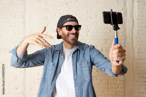 Keuken foto achterwand Retro young attractive latin man taking a selfie with his smart cell phone.