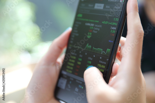 Canvas Prints Textures Close up on woman hand holding smartphone trading stock and data in coffee shop background business concept