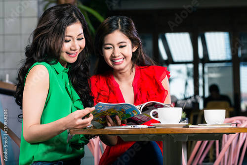 Photo  Two beautiful young women smiling while looking together at a trendy magazine du