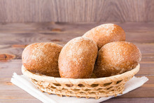 Fresh Rye Buns In A Basket On A Wooden Table