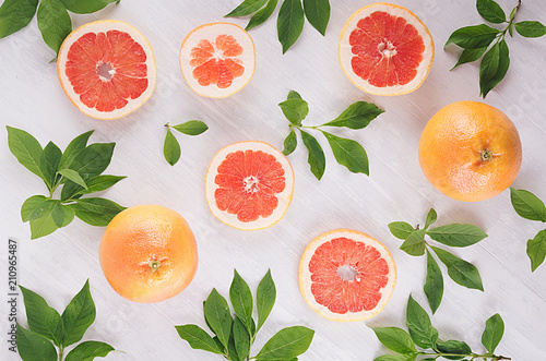 Slices grapefruit and green leaves on soft white wooden background, pattern, top view.