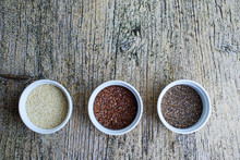 Three Superfoods Chia, Flax And Sesame Seeds In White Pals On A Wooden Background