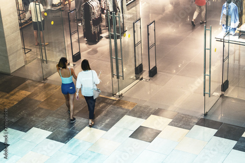Fotografía  Silhouettes of Two Women Goes to the Clothing Store