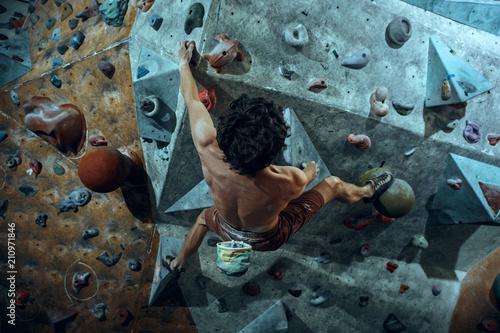 Canvas Print Free climber young man climbing artificial boulder indoors