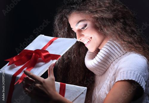 Fotografia, Obraz  Portrait of a beautiful young brunette peering in a gift box