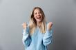 Leinwanddruck Bild - Portrait of a happy young blonde girl celebrating success