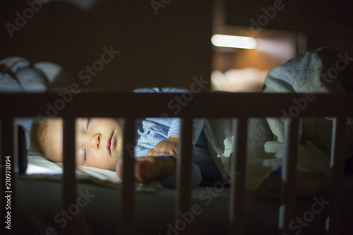 Photo Adorable newborn baby boy, sleeping in crib at night