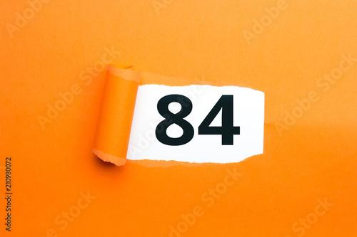 Photo  Zahl vierundachtzig - 84 verdeckt unter aufgerissenem orangen Papier