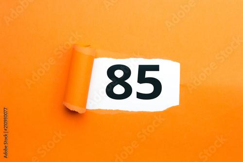 Fotografia  Zahl fünfundachtzig - 85 verdeckt unter aufgerissenem orangen Papier