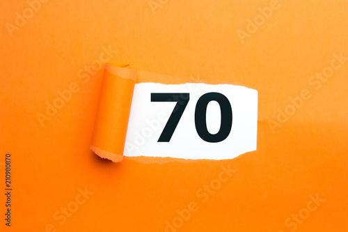 Fotografia  Zahl siebzig - 70 verdeckt unter aufgerissenem orangen Papier