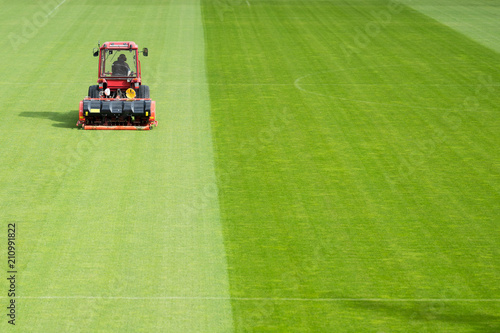 Man in tractor aerating a soccer field Tablou Canvas