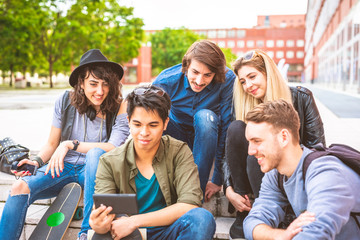 group of friends multiethnic sitting outdoor using smart phone streaming online - video, portable television, technology concept