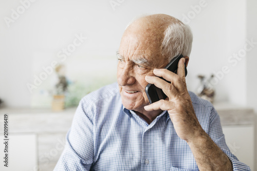 Happy senior man using smartphone at home