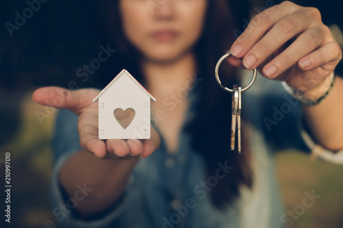 Fotografia, Obraz  Woman hand holding house key for new owner. Property home sale.