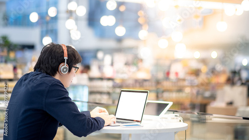 Canvas Print Young Asian business man listening to music by headphones while working with laptop computer in co working space