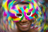 Salvador Carnival scene features samba dancing Brazilian man smiling in colorful mask in Pelourinho, Slow shutter speed and motion blur