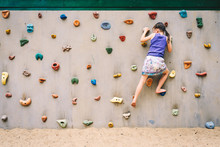Little Girl Climbing A Rock Wa...