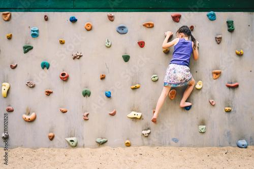 little girl climbing a rock wall outdoor at children playground