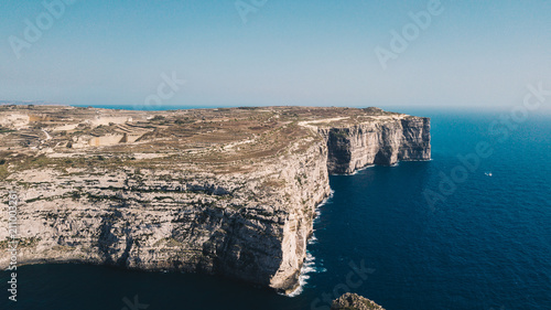Staande foto Kust Beautiful aerial view of dramatic high precipice with beautiful sea view. Yacht sailing boat in the sea. Drone top view shot of dangerous stony cliffs. Gozo island, Malta