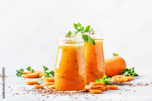 Carrot juice with flax seeds in glass bottles, healthy drink for raw diet, selective focus