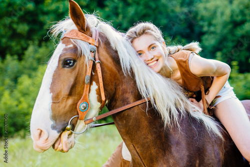 Portrait of happy smiling woman cowgirl, riding a brown horse Wallpaper Mural