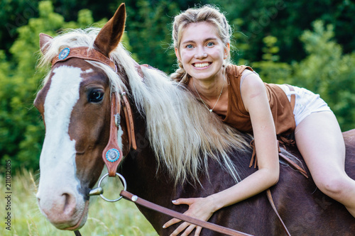 Tuinposter Ontspanning Portrait of happy smiling woman cowgirl, riding a brown horse. Clothed white jeans shorts, brown leather vest. Has slim sport body. Portrait nature. People and animals friendship concept.