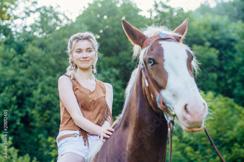 Tuinposter Ontspanning People and animals friendship, hippotherapy concept. Portrait of happy pensive woman cowgirl, riding a brown horse. Clothed white jeans shorts, brown leather vest. Has slim sport body.