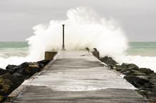 A Wave Crashes Over The End Of A Pier In Windy Conditions