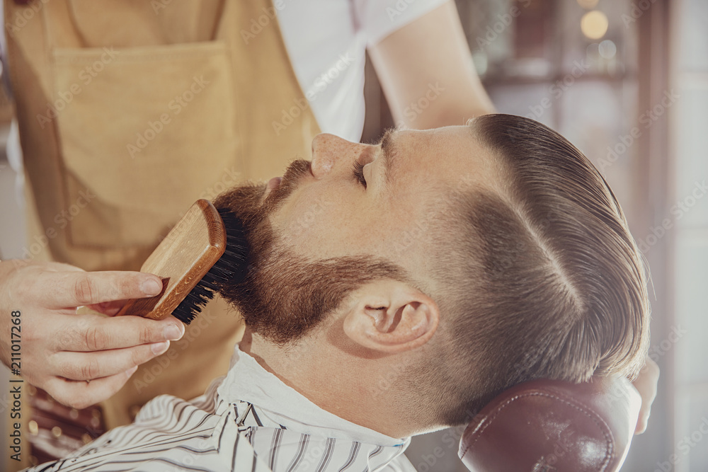 Fototapeta The barber combs the man's beard with a brush. Photo in vintage style