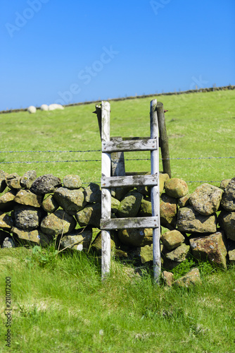 Fotografie, Obraz  A wooden stile over a dry stone wall and barbed wire, County Antrim, Northern Ireland