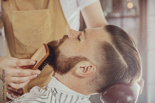 Fotografie, Obraz The barber combs the man's beard with a brush