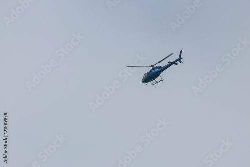 Helicopter flying in blue sky Poster