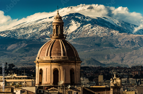 Stampa su Tela The dome of Cathedral in Catania on the background of volcano Etna in the snow