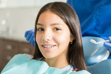 Portrait Of Smiling Teenage Girl With Braces In Clinic