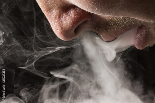 Fotografie, Obraz  gray cigarette smoke comes from an open mouth of a smoker