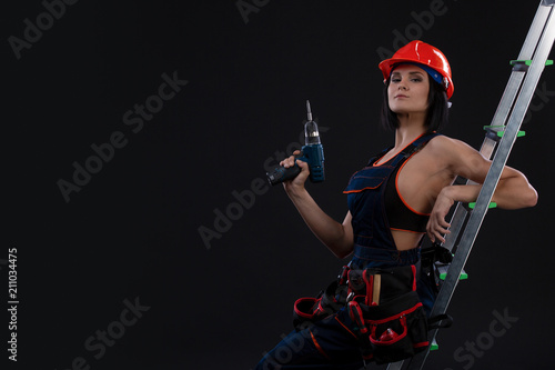 Beautiful woman with a drill on a ladder ready to use it