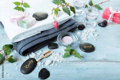 Spoed Foto op Canvas Spa Spa setting on blue wooden rustic table. Natural sea salt, candles, handmade soap, flowers, towels. Spa resort therapy composition, spa concept. Top view