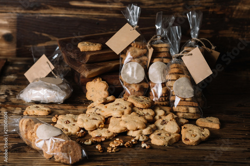 Fototapety, obrazy: Packs of homemade biscuits and scattered biscuits on wood background