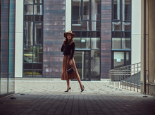Fashion Elegant Woman Wearing A Black Jacket, Brown Hat And Skirt With A Handbag Clutch Walking On The European City Center.