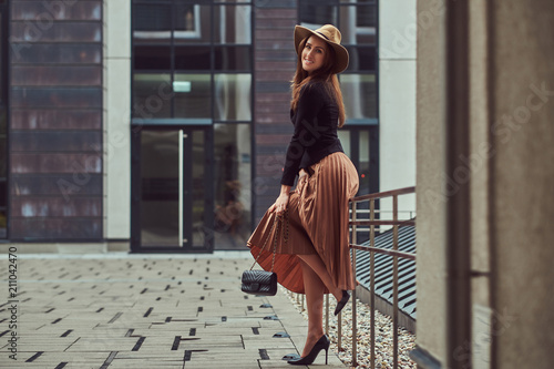 Juliste  Smiling fashion elegant woman wearing a black jacket, brown hat and skirt with a handbag clutch posing while leaning on a steel railing on the European city center