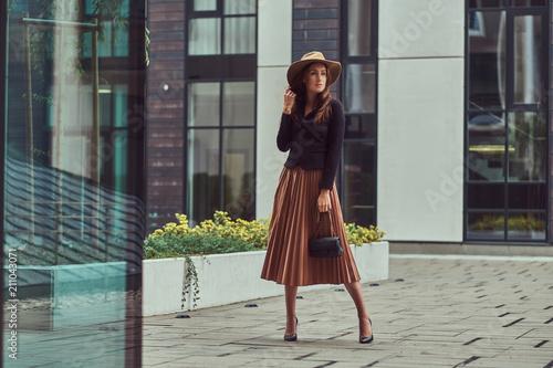 Fashion elegant woman wearing a black jacket, brown hat and skirt with a handbag clutch walking on the European city center Fototapeta