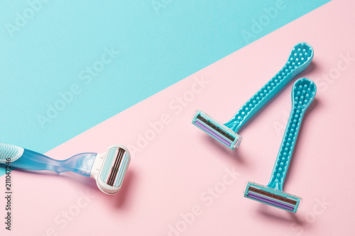 two disposable blue razors and one reusable on pink background