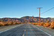 Single country road in the Mojave Desert facing mountains in a early morning drive.