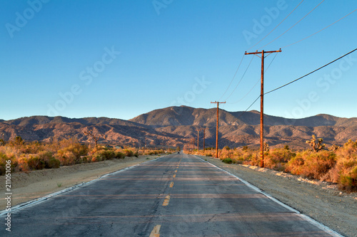 Fototapety, obrazy: Single country road in the Mojave Desert facing mountains in a early morning drive.