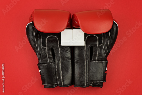 leather boxing gloves hold the wooden calendar on red background