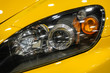 Luxury yellow car headlight close-up. Concept of expensive, sports auto. The concept of tuning. Headlight of modern prestigious car.