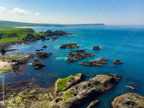 In de dag Kust Vivid emerald-green water at Ballintoy harbour along the Causeway Coast in County Antrim, Northern Ireland.