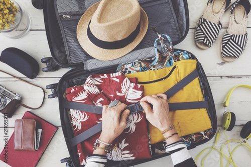 Fototapeta Woman hand preparing summer luggage
