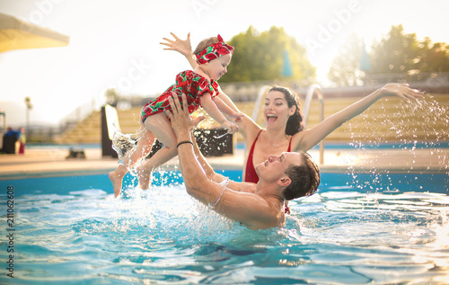 Beautiful family having fun in a swimming pool Slika na platnu